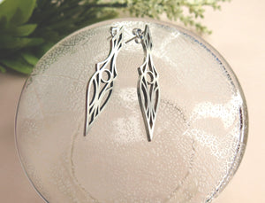 Art Deco stud earrings on a glass plate. Symmetrical and geometric modern design.