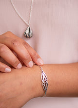 Load image into Gallery viewer, Sterling silver art deco mirrored teardrop bracelet on a model's wrist with art deco fig necklace in the background