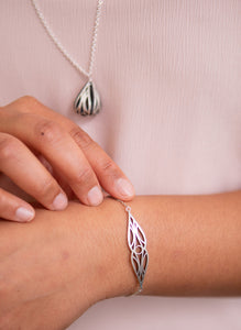 Sterling silver art deco mirrored teardrop bracelet on a model's wrist with art deco fig necklace in the background