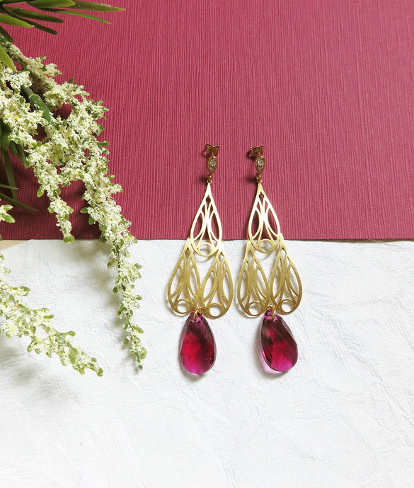 Gold Art Deco inspired chandelier earrings with berry red tear drop shaped swarovski crystals. The earrings are resting on a deep red coloured paper