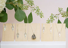 Load image into Gallery viewer, A collection of sterling silver geometric art deco teardrop and dagger jewellery on pale wood panels. From left to right: teardrop stud earrings, teardrop hoop earrings, fig pendant necklace, dagger stud earrings, and teardrop pendant necklace. With flowers and leaves behind.