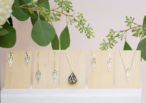 A collection of sterling silver geometric art deco teardrop and dagger jewellery on pale wood panels. From left to right: teardrop stud earrings, teardrop hoop earrings, fig pendant necklace, dagger stud earrings, and teardrop pendant necklace. With flowers and leaves behind.
