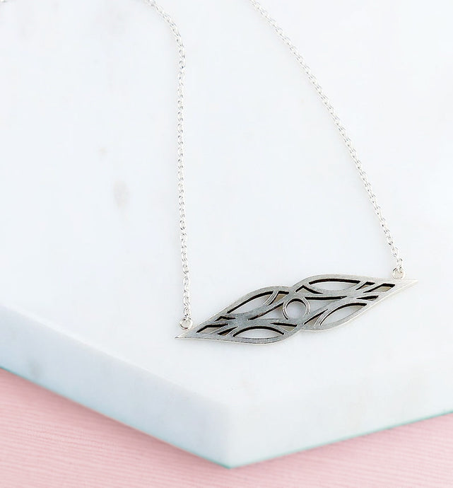Sterling silver art deco double teardrop symmetrical necklace with sterling silver chain, sitting on white marble and pink background.