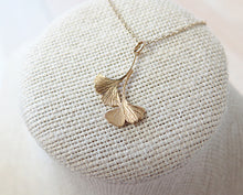 Load image into Gallery viewer, A gold double ginkgo leaf pendant necklace. Assymetrical and textured with a bright shiny finish. The pendant and gold chain are resting on a fabric pedestal.