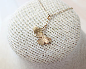A gold double ginkgo leaf pendant necklace. Assymetrical and textured with a bright shiny finish. The pendant and gold chain are resting on a fabric pedestal.