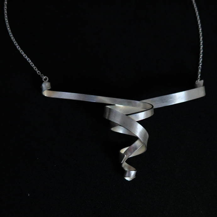 A modern sterling silver helix spiral ribbon pendant necklace on a black background.