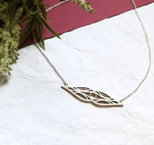 Load image into Gallery viewer, Art deco double teardrop symmetrical sterling silver necklace in high-sheen brushed finish oxidized for contrast. On a silver chain. On white and burgundy textured paper and a sprig of flowers.