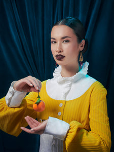 A model with dark lipstick is holding an orange. She is wearing gold art deco inspired earrings, a white shirt with a frilled collar, and a yellow sweater.