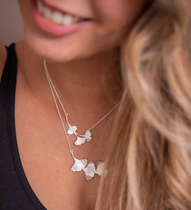 A woman wearing two ginkgo leaf necklaces. The sterling silver leaves are textured and shiny.