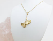 Load image into Gallery viewer, A gold pendant necklace of two assymetrical and organically textured ginkgo leaves with a gold chain on a white jewellery stand.