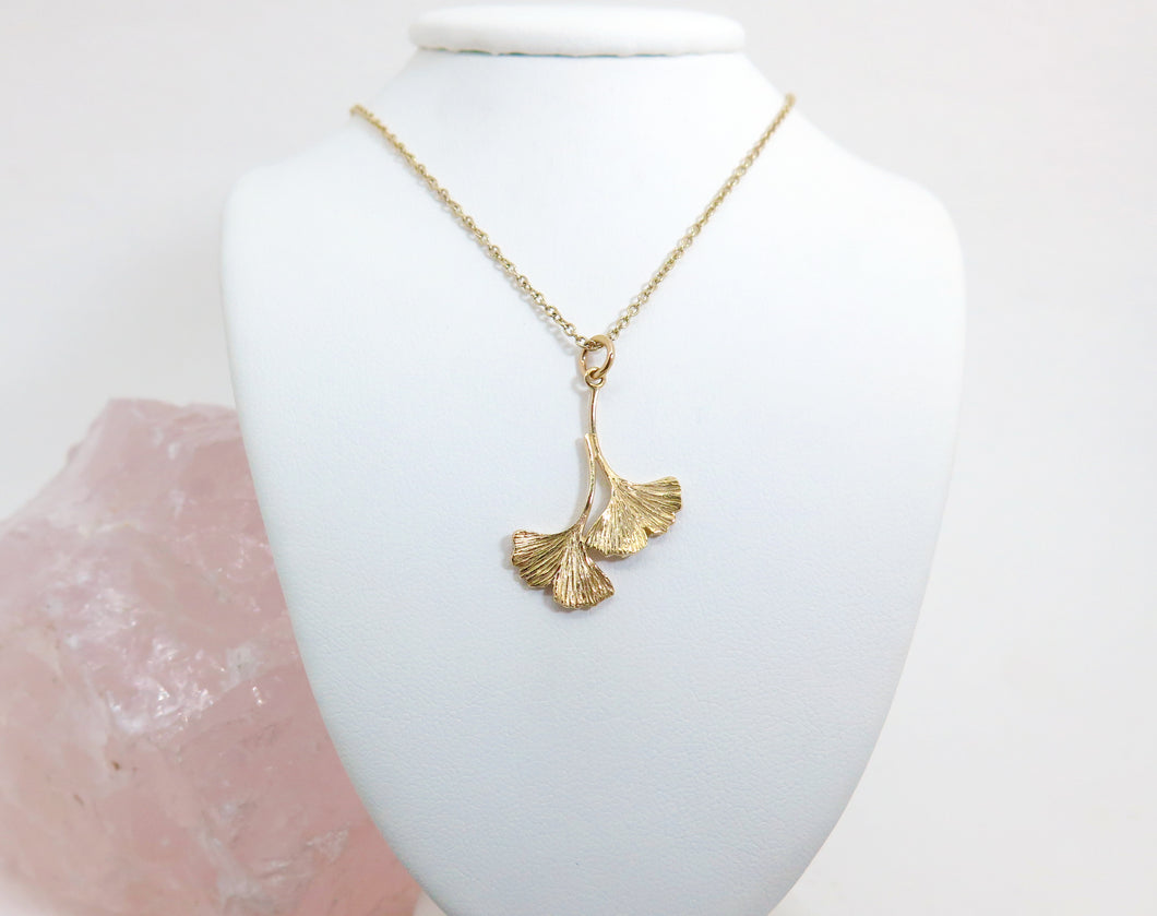 A gold double ginkgo leaf pendant necklace. Assymetrical and textured with a bright shiny finish. On a gold chain hanging on a white jewellery stand.