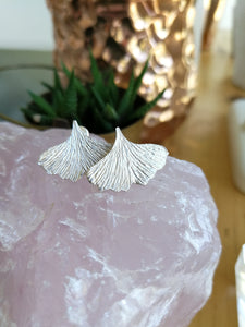 Textured sterling silver ginkgo leaf shaped stud earrings resting on a piece of rose quartz with a plant in the background
