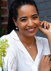 A smiling woman wearing ginkgo leaf dangle earrings and a necklace with three small ginkgo leaves