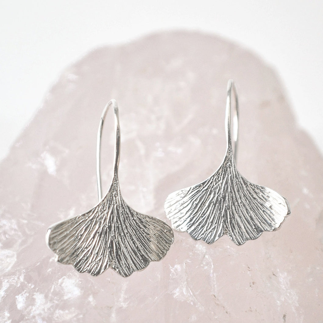 Textured sterling silver ginkgo leaf shaped dangle earrings resting on a piece of rose quartz