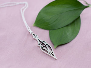 Sterling silver geometric art deco dagger pendant necklace  on a pink background with leaves