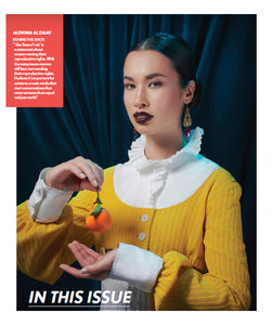 "A photo of a magazine page with a model with dark lipstick is holding an orange. She is wearing gold art deco inspired earrings, a white shirt with a frilled collar, and a yellow sweater. There is a blurb about Jazmina Alzaiat, the photographer, and the  creative photograph ""She Bears Fruit""."