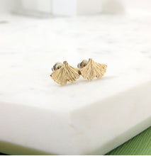 Load image into Gallery viewer, Textured gold ginkgo leaf stud earrings resting on a piece of marble