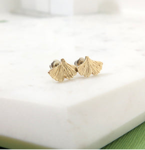 Textured gold ginkgo leaf stud earrings resting on a piece of marble