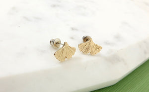 Textured gold ginkgo leaf earrings resting on a piece of marble