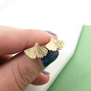 Textured gold ginkgo leaf stud earrings in a hand with nail polish on the nails.