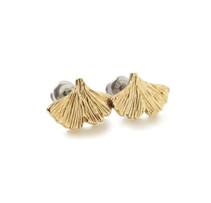Gold ginkgo leaf shaped earrings with texture on a white background