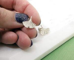 Textured sterling silver ginkgo leaf stud earrings in a hand with nail polish on the nails.