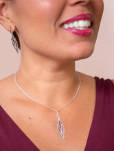 Load image into Gallery viewer, Model in a burgundy dress wearing a geometric art deco pendant necklace and matiching stud earrings.