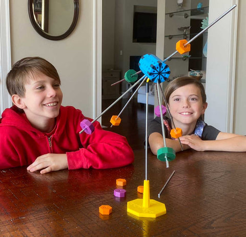 Two children looking at a balanced Octacog contraption