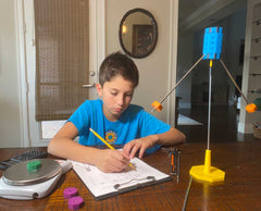 Boy using a scale with Octacog to take measurements and record data.