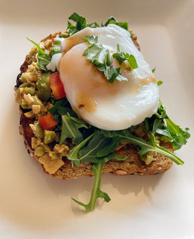 Avocado toast on wheat bread with poached egg, parmagiano tapenade, olives