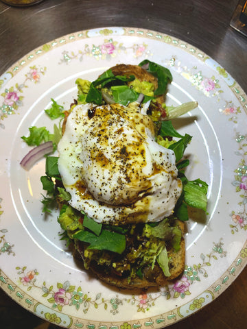 avocado toast with poached egg and balsamic vinegar and parmagiano tapenade