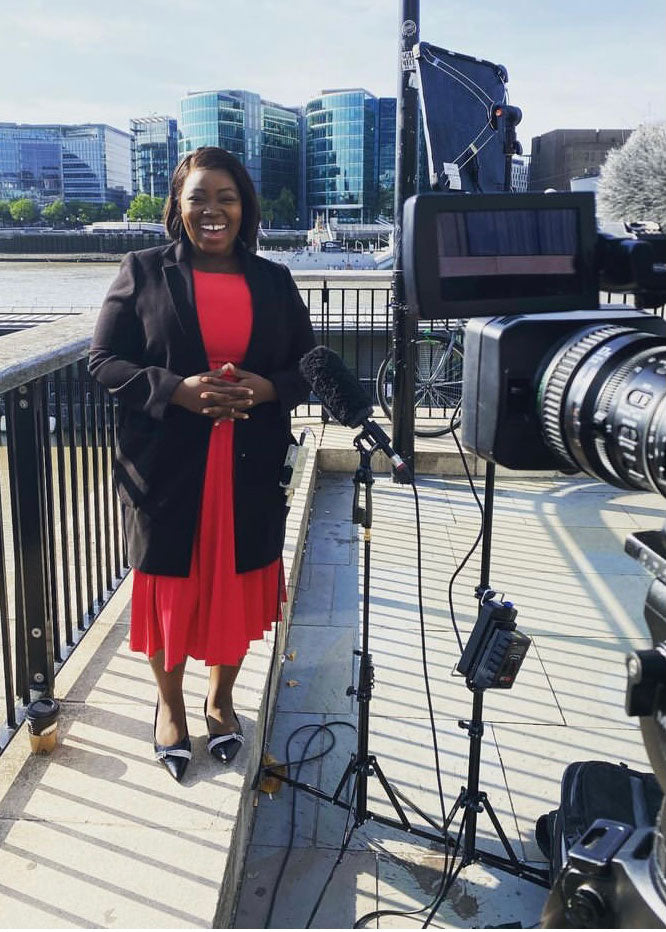 Female journalist standing in front of the camera in central London