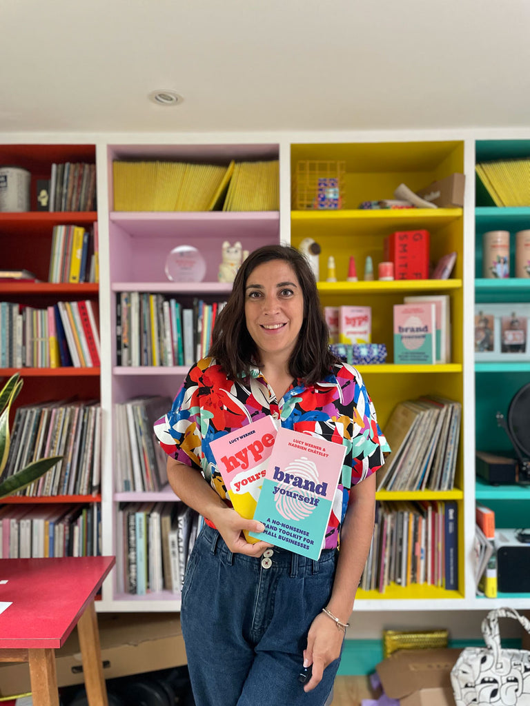 PR expert Lucy Werner standing in front of her bookshelf with her two new books