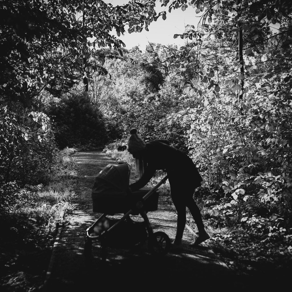 A black and white image of Katerina and her Ocarro Moon pushchair in a wooded area.
