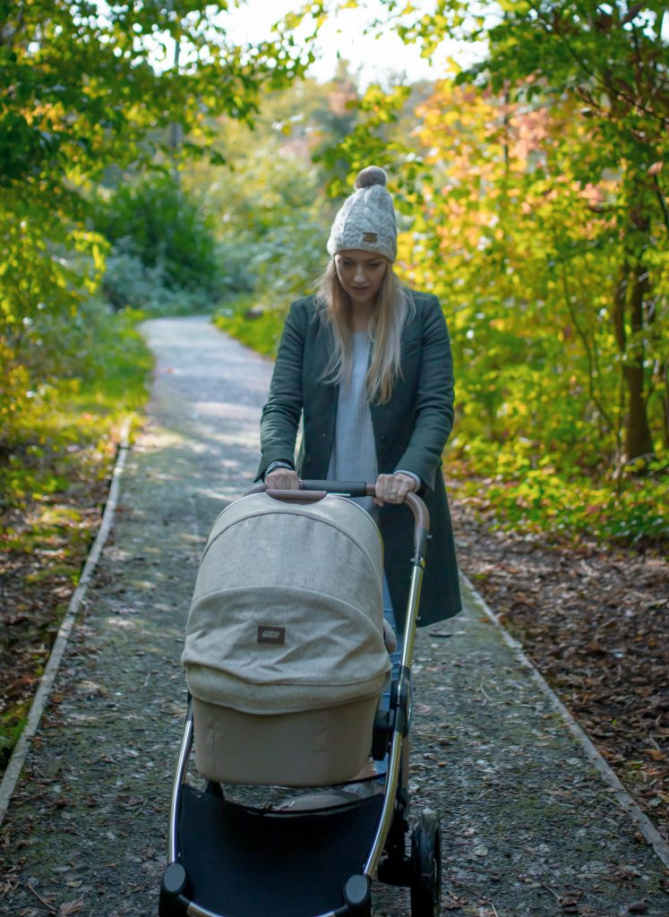 Katerina pushing her Ocarro Moon pushchair along a woodland path.