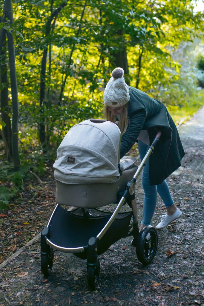 Katerina is attending to her baby while it is in the Ocarro Moon pushchair carrycot, they are walking through the woods.