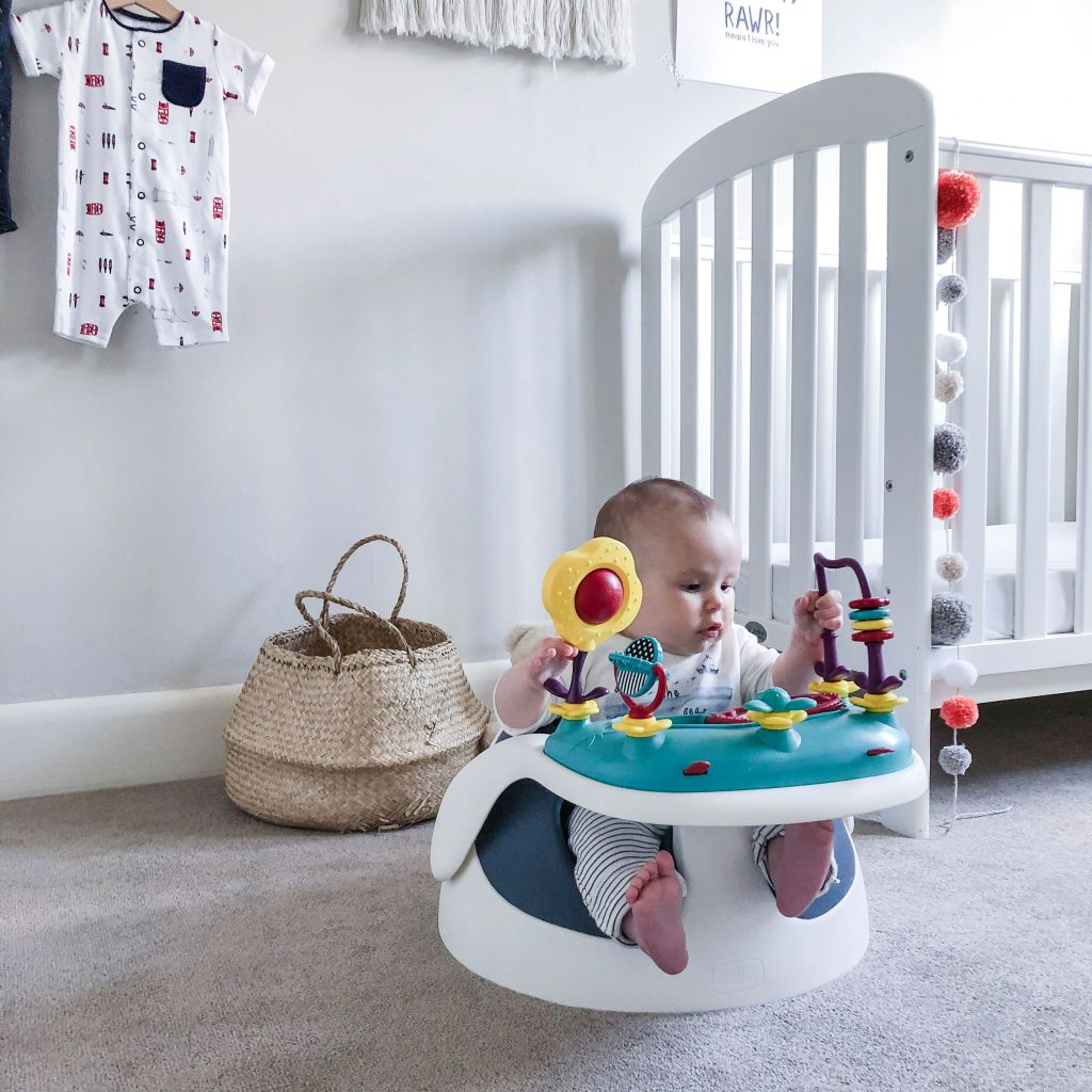 Another shot of baby Marlow playing with the interactive play accessory attached to the tray of the Baby Snug booster seat.