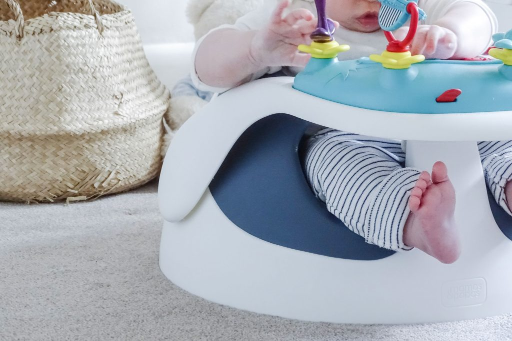 A close up of the Baby Snug booster seats wide base. Baby Marlow is sat in it, playing with the toy tray.