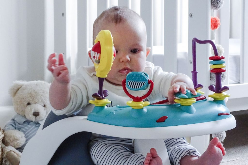 Baby Marlow is sat in the Baby Snug Booster Seat in his nursery. There is a cot behind him and he is playing with the interactive play tray attached to the seat.