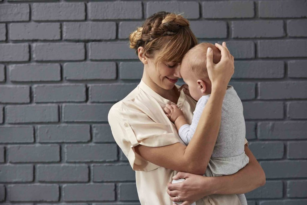 A mother is stood in front of a brick wall, affectionately cuddling her baby who is playing with the buttons on her shirt.