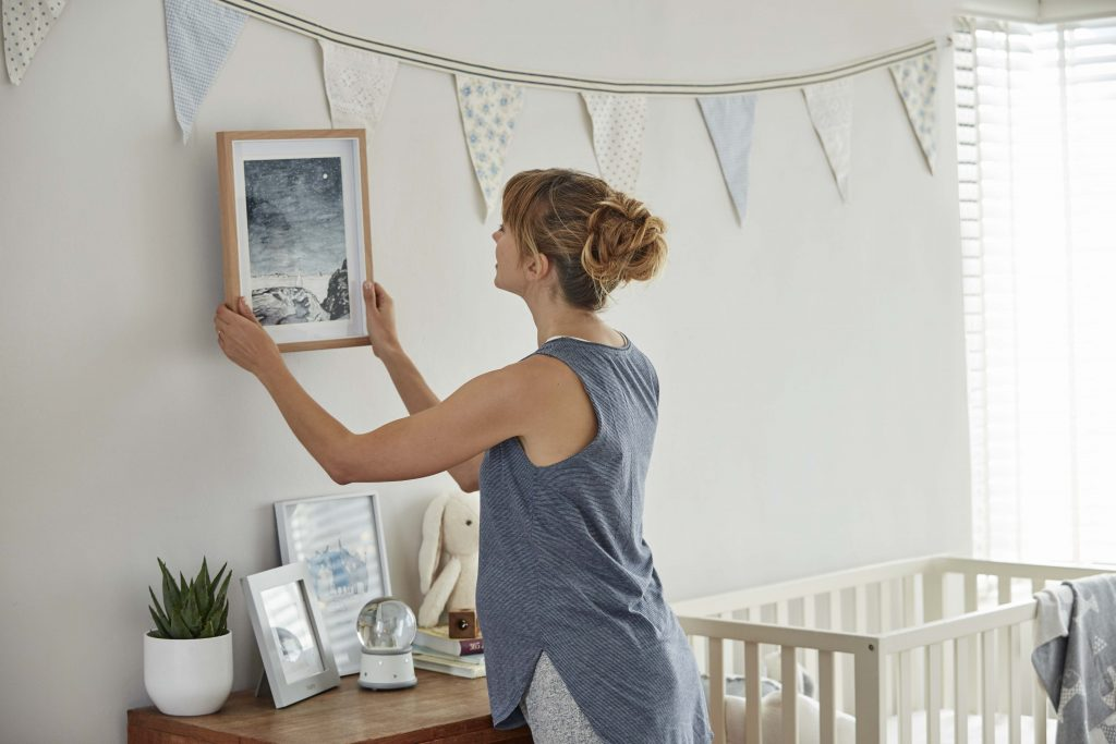 A pregnant woman hangs a picture in a bright nursery that has been freshly decorated and furnished with a cot, bunting, a dresser and an array of ornaments.