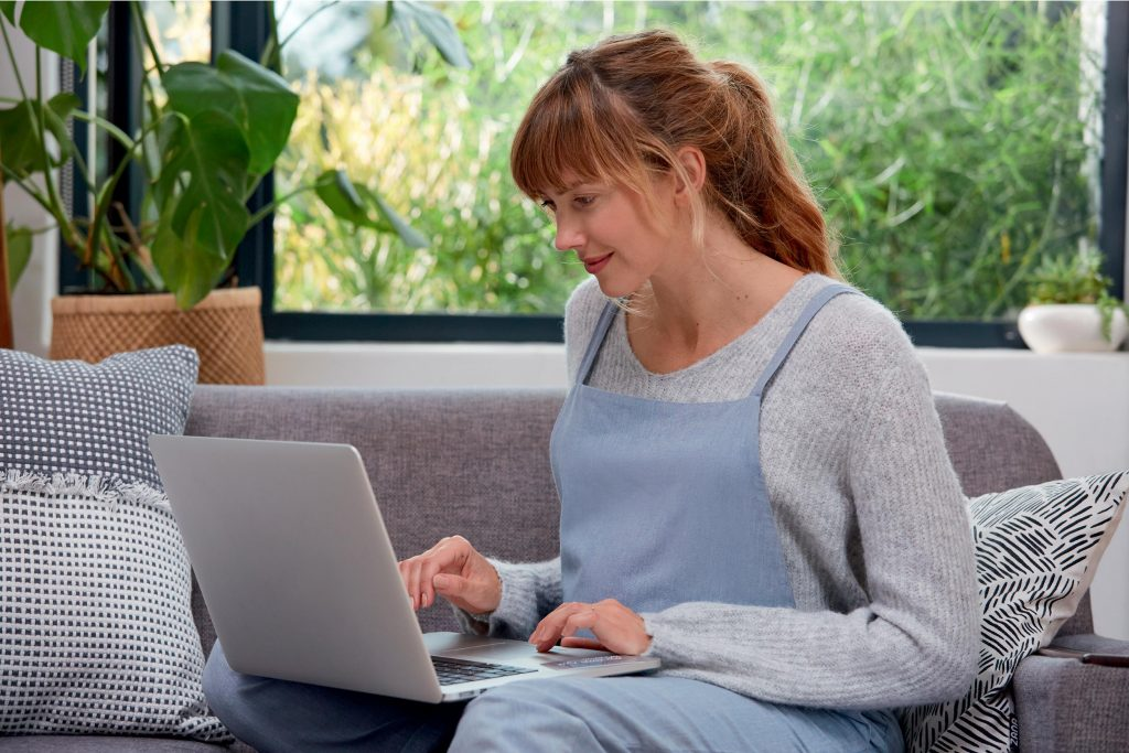 A pregnant woman is sat on a sofa in a brightly lit living room with an open laptop. She is typing on the laptop.