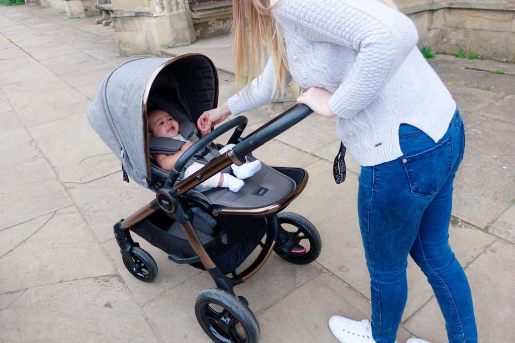 Haley is pushing baby Elodie in the Ocarro pushchair along a pavement, she is reaching inside the pushchair to settle the baby.