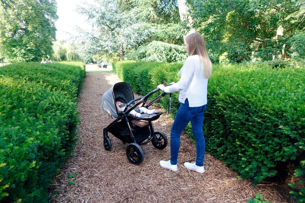 An image of Haley with the Ocarro pushchair, she is walking away from the camera with baby Elodie in the pushchair.