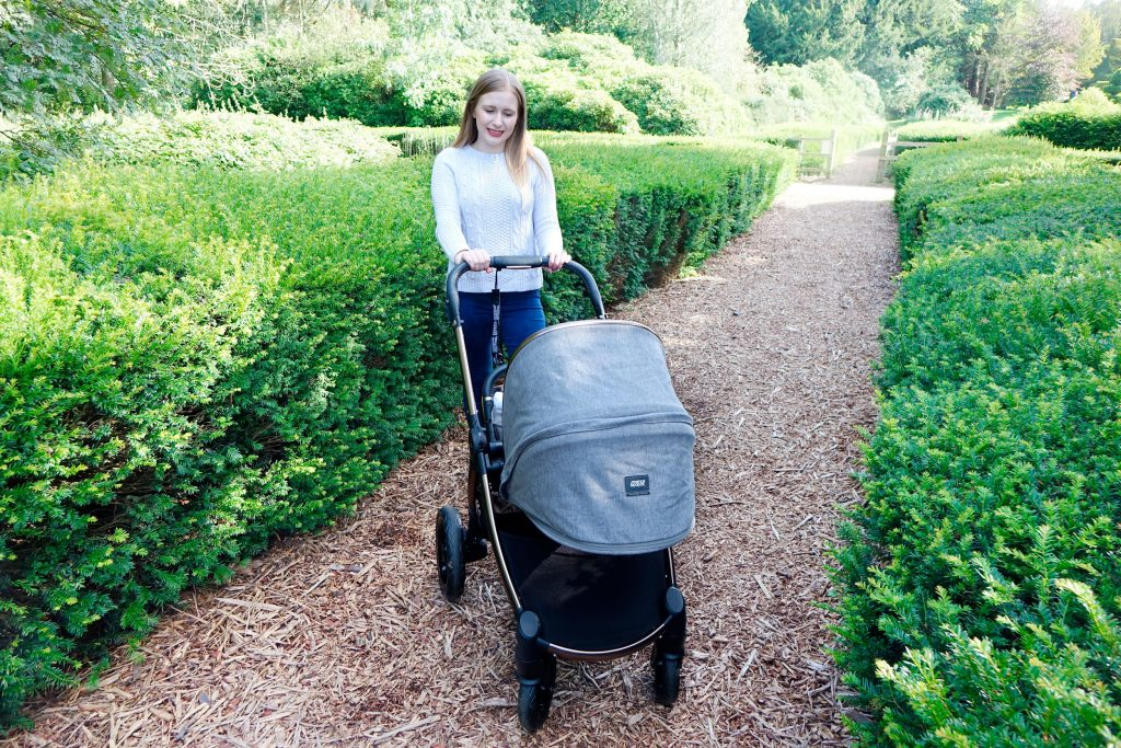 Haley is posing with the Ocarro pushchair in a park.