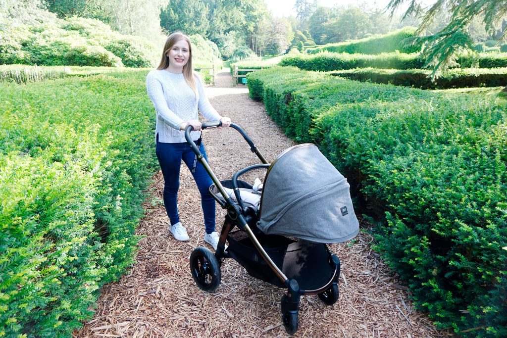 Haley is posing with the Ocarro Simply Luxe pushchair in a park, on a gravel path, between rows of bushes.