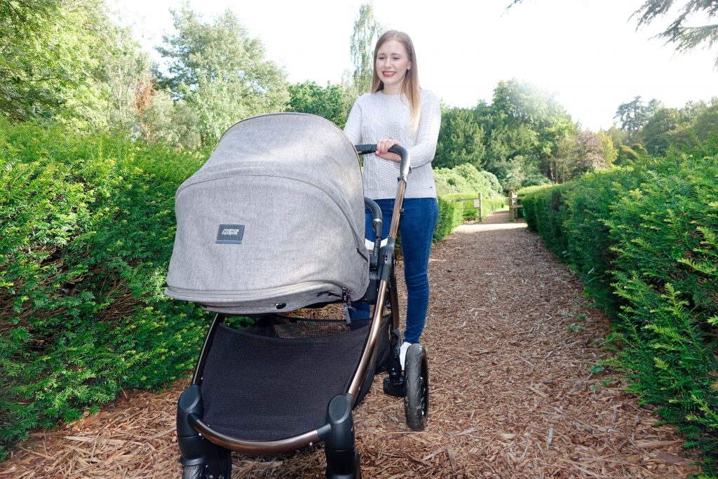 Haley is pushing the Ocarro pushchair along a gravel path between two rows of hedges.