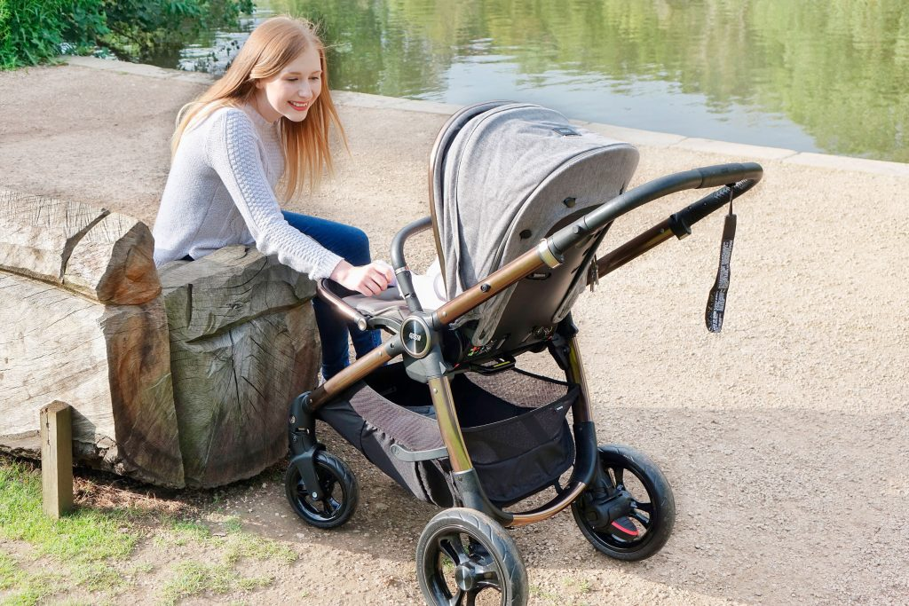 Haley is sat on a park bench next to a pond, she has the Ocarro pushchair next to her and she is entertaining baby Elodie who is sat inside.
