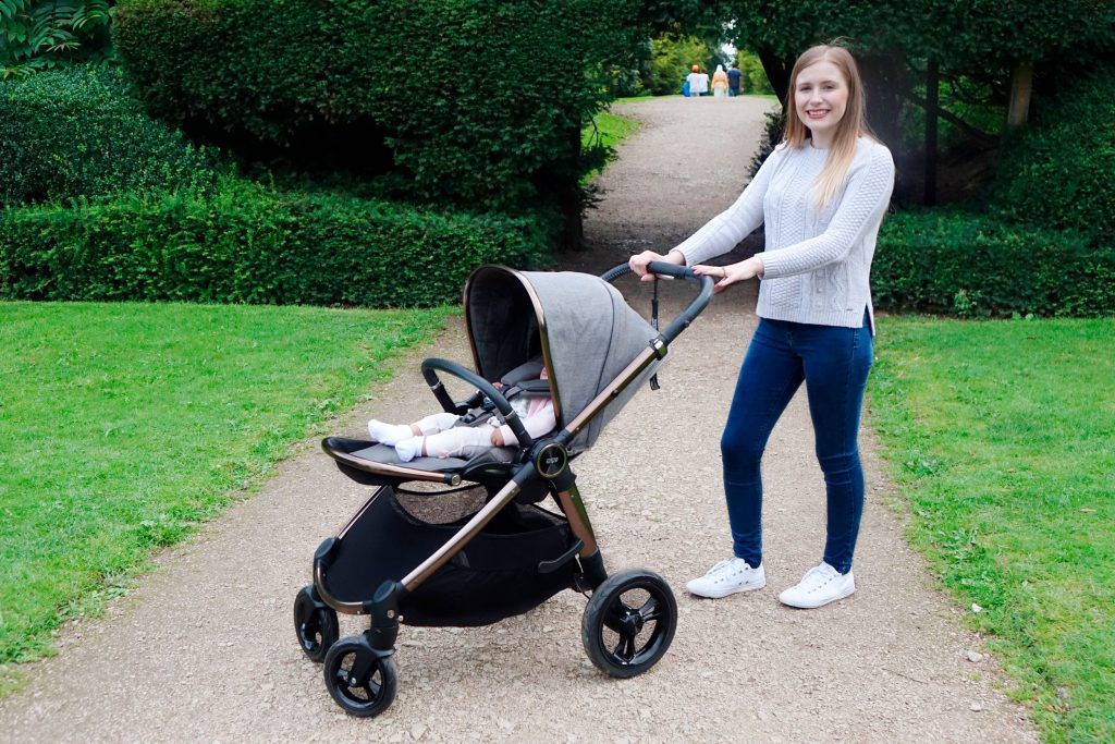 Haley is posing with the Ocarro pushchair, baby Elodie is in the forward-facing seat.
