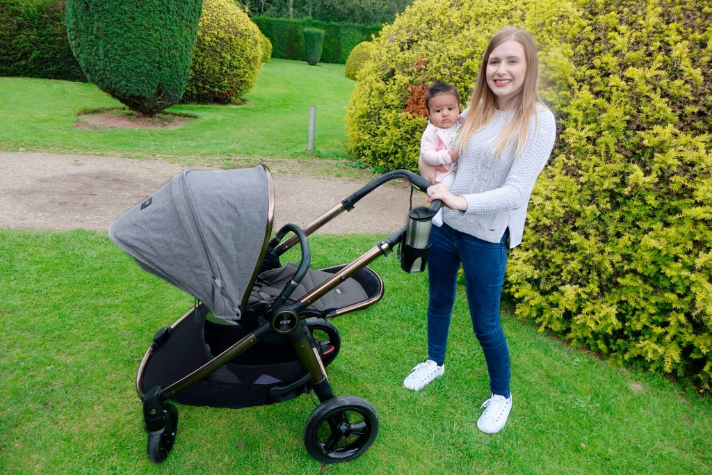 Haley is carrying baby Elodie and they are posing with the Ocarro pushchair, behind them is a hedge.